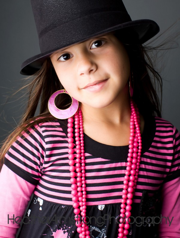girl modeling hat and jewelry for photographer