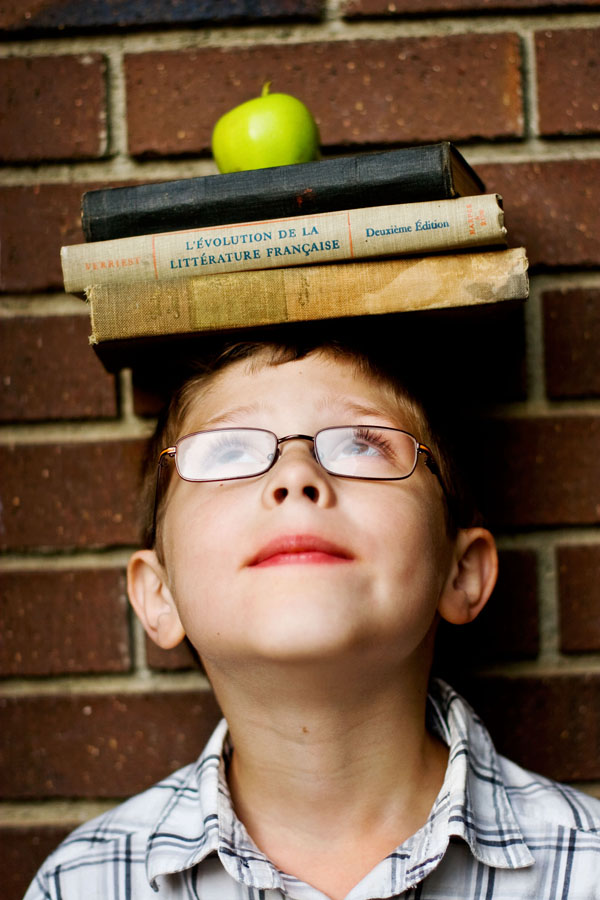 boy with books and apple on head