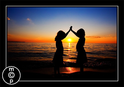 silhouette of twin girls at sunset