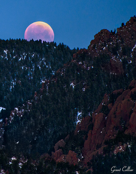 Eclipsed moon setting over Rocky Mountains