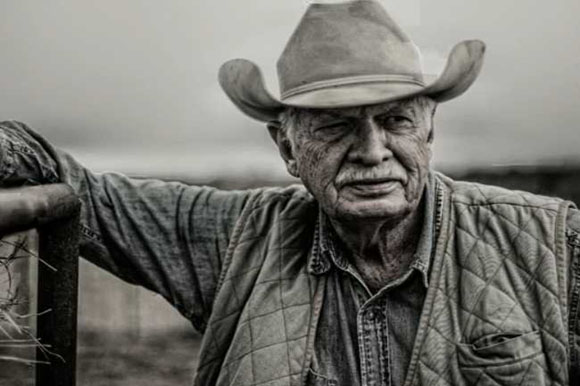 Black and white portrait of farmer leaning against fence