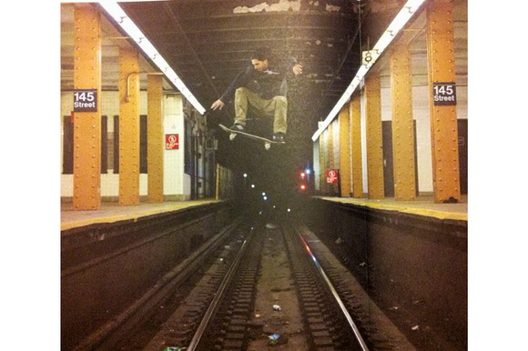 Image of skateboarder ollieing over subway tracks in New York City